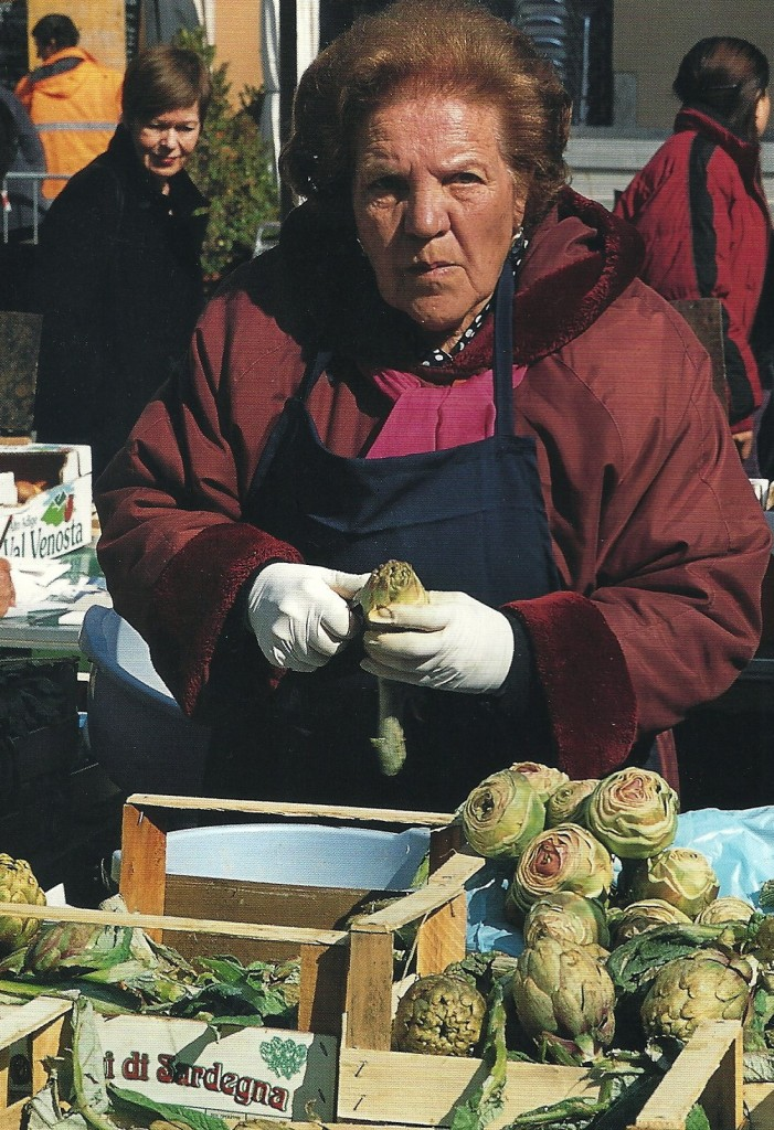 Vendor trimming artichokes grown in Sardegna at the Campo dei Fiori market in Rome. From Roma: Authentic Recipes from n and Around the Eternal City, by Julia della Croce (chronicle Books)  Photo: Paolo Destefanis