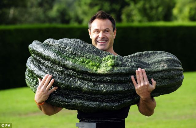 """A Day in the life of a weightlifter,"" Jonathan Walker lifts a 120-pound marrow after Peter Glazebrook won the Giant Marrow Class. Photo and story: Daily Mail Online, U.K., copyright PA"