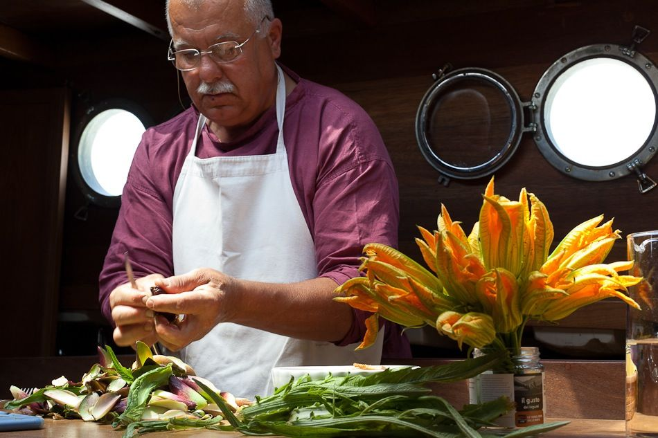 Mauro teaches how to stuff zucchini blossoms on board the Eolo. Photo: Paolo Spigariol