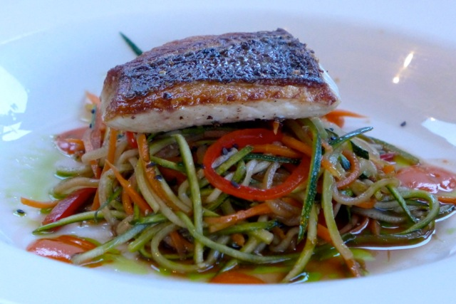 Seared fresh water fish, on a bed of vegetables.