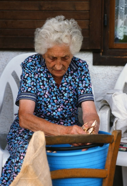 Woman shucking beans, Lamon